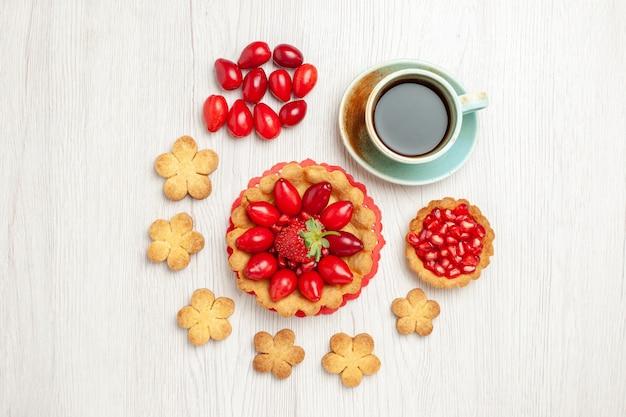 Vista dall'alto piccola torta con biscotti di frutta e tazza di tè sulla scrivania bianca
