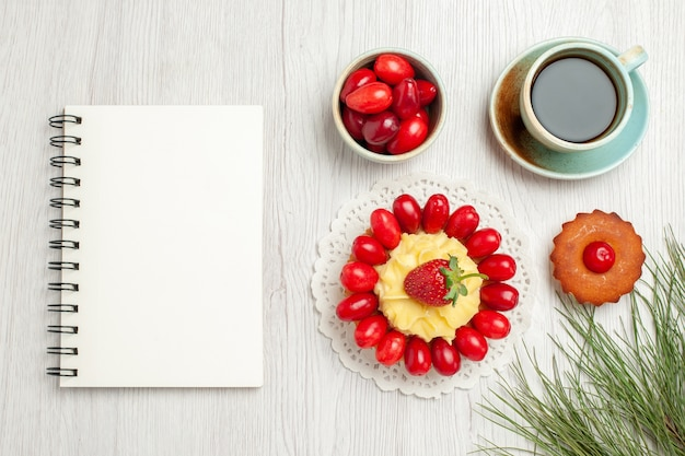 Vista dall'alto piccola torta con frutta e tazza di tè sulla scrivania bianca