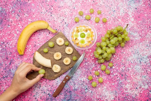 上面の明るい表面のフルーツケーキの新鮮なまろやかな色のブドウとバナナの小さなケーキ