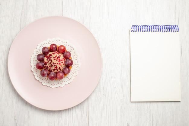 白いテーブルの上のプレート、フルーツデザートケーキの中にブドウの上面図小さなケーキ