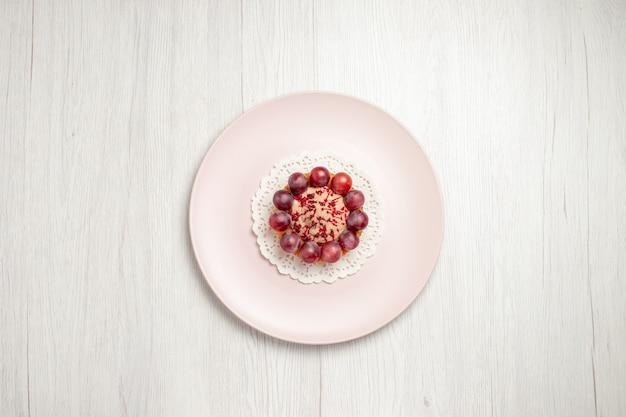 Vista dall'alto piccola torta con l'uva all'interno del piatto sul tavolo bianco, torta di frutta dolce