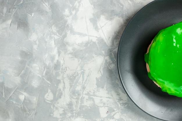 Vista dall'alto piccola torta con glassa verde su sfondo bianco chiaro torta torta biscotto biscotti di zucchero dolce