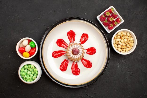 Torta vista dall'alto con caramelle alle noci e frutta su zucchero di frutta color caramella superficie scura