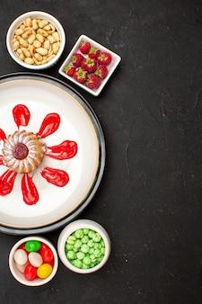 Vista dall'alto piccola torta con noci, caramelle e frutta su superficie scura caramella colore frutta zucchero dolce