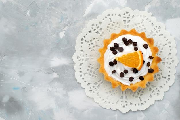 上から見る甘い灰色の机の上のオレンジスライスとクリームの小さなケーキ