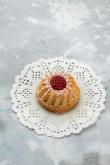 灰色の机の上のラズベリーと上面の小さなケーキ