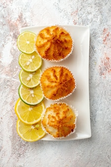 Top view little cakes baked and  with lemon slices on white surface