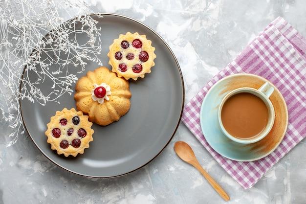 Vista dall'alto piccole torte all'interno della lastra grigia con caffè al latte sulla scrivania leggera torta al caffè dolce
