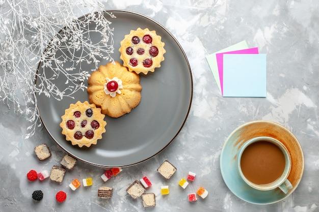 ホワイトグレーのデスクケーキの甘い砂糖焼きにミルクコーヒーと灰色のプレート内の小さなケーキの上面図