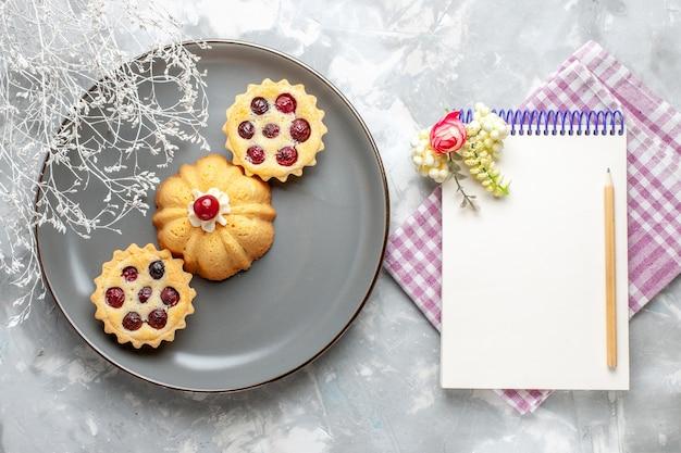 明るい背景のケーキ甘い砂糖焼きフルーツにメモ帳と灰色のプレート内の小さなケーキの上面図