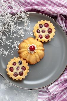 Вид сверху маленькие пирожные внутри тарелки на сером столе бисквитная сладкая выпечка крем цветное фото