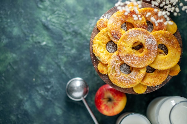 Top view little cakes in pineapple ring shape with milk on dark background fruit pie pastry cake hotcake color bake