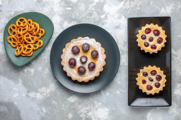 平面図灰色の机の上の果物とポテトチップスで粉末化された小さなケーキ砂糖フルーツビスケットケーキ甘い砂糖