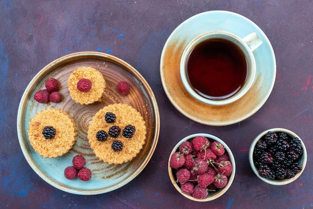 Vista dall'alto di piccole torte dolci e deliziose con frutti di bosco freschi e tè sulla superficie scura