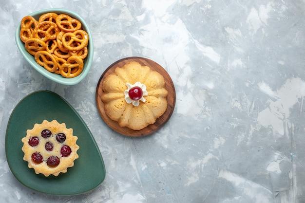 Vista dall'alto piccole torte con ciliegie insieme a cracker sullo sfondo chiaro torta biscotto croccante dolce foto a colori