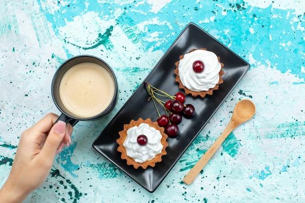 上面図水色のデスクケーキにさくらんぼと牛乳の小さなケーキは甘いパイの果実を焼く