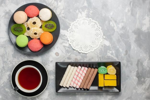 Вид сверху маленькие пирожные с печеньем, чашка чая и печенье на белом фоне, печенье, печенье, сладкий сахарный пирог, чай