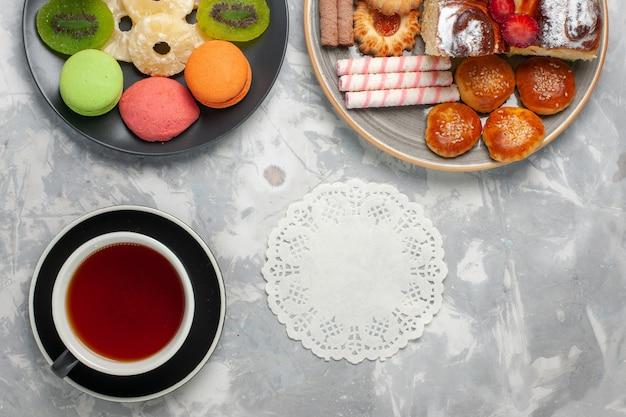 上面図白いバックグラウンドクッキービスケット甘い砂糖パイティーにお茶とデザートのクッキーカップと小さなケーキ