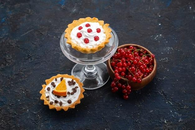Вид сверху маленькие пирожные со сливками вместе со свежей красной клюквой на темной поверхности сладких фруктов