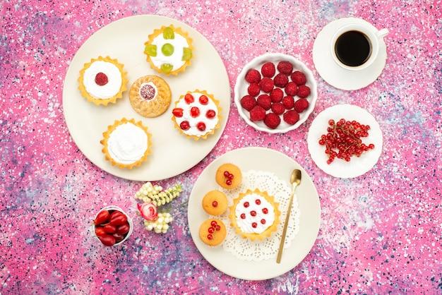 Vista dall'alto piccole torte con crema di frutta fresca e insieme a una tazza di caffè all'interno del piatto bianco sul tè luminoso della scrivania
