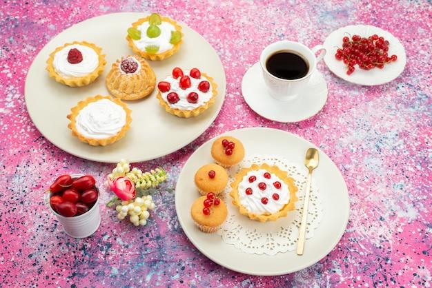 トップビュークリームフレッシュフルーツと明るい机の上の白い皿の中のコーヒーカップと一緒に小さなケーキ