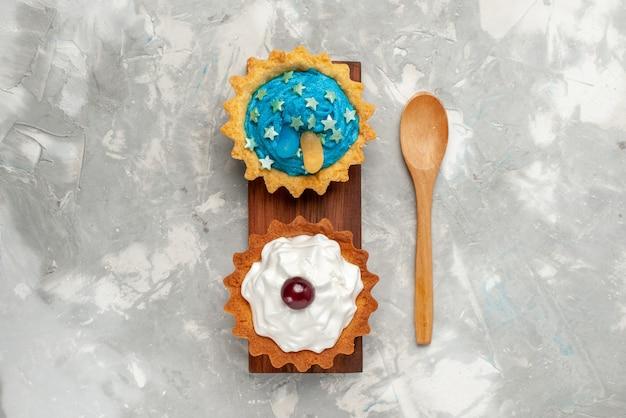 明るい背景のケーキの甘い砂糖焼きの明るい背景のケーキクリーム砂糖甘い焼きのクリームとトップビューの小さなケーキ