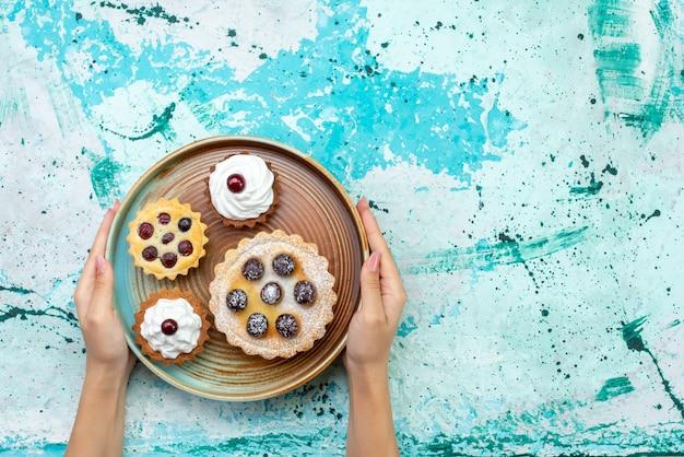 Vista dall'alto piccole torte con crema di zucchero in polvere frutti sullo sfondo azzurro torta crema biscotto zucchero dolce cuocere