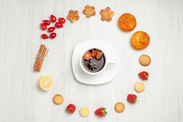 Vista dall'alto piccole torte con una tazza di tè sulla scrivania bianca