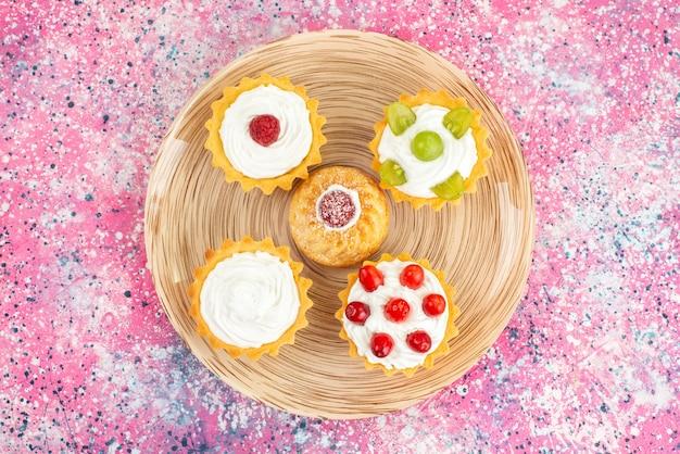 Вид сверху маленькие пирожные со свежими сливками и фруктами на яркой поверхности печенья