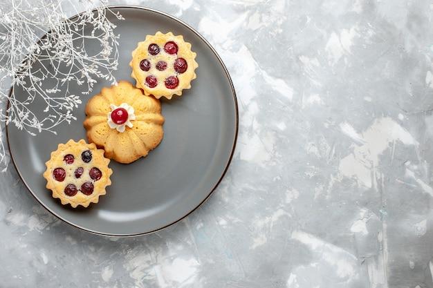 Vista dall'alto piccole torte con frutta all'interno della lastra grigia sullo sfondo chiaro torta biscotto zucchero dolce colore