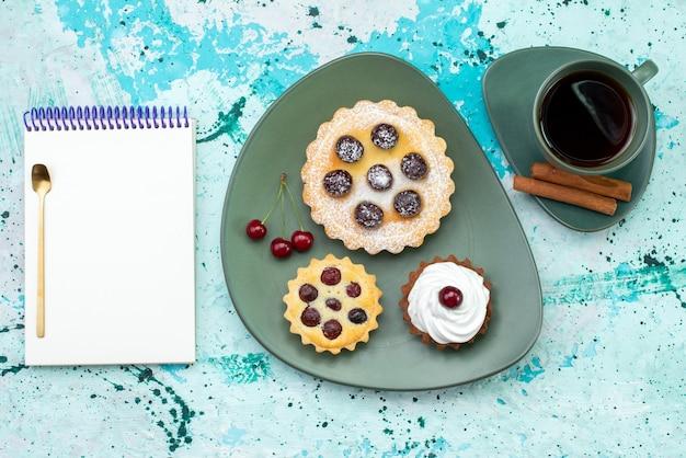 水色のテーブルケーキの上のお茶とメモ帳と一緒にプレートの中に果物が入った小さなケーキの上面図は甘い砂糖茶の色を焼きます