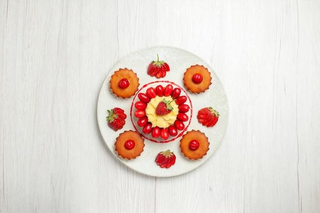 白い机の上のプレートの中に果物と小さなケーキの上面図