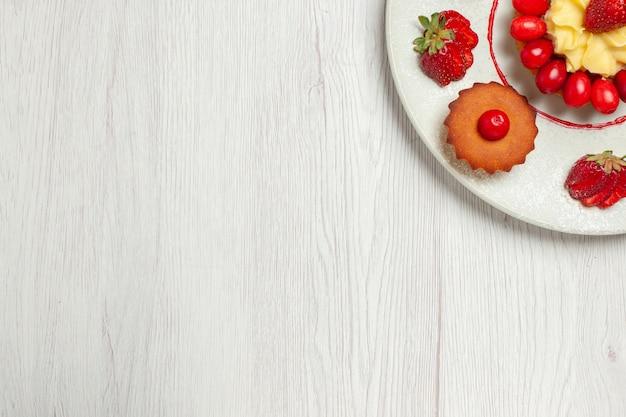Vista dall'alto piccole torte con frutta all'interno del piatto sulla scrivania bianca