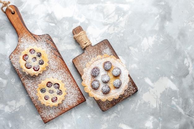 Vista dall'alto piccole torte con frutta su sfondo chiaro torta biscotto dolce cuocere
