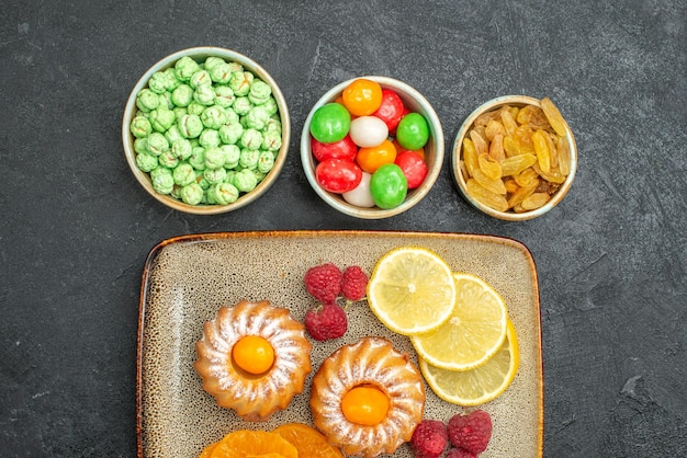 Top view of little cakes with lemon slices tangerines and candies on black