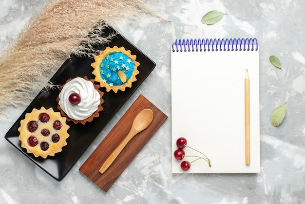 明るい背景の上のメモ帳と小さなケーキの上面図ケーキパイクリーム甘い砂糖の写真