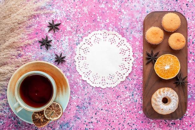 Vista dall'alto di piccole torte con fetta d'arancia e tazza di tè sulla superficie rosa chiaro