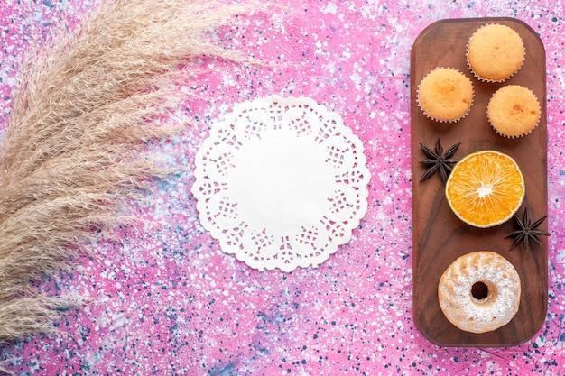 Vista dall'alto di piccole torte con fetta d'arancia su superficie rosa chiaro