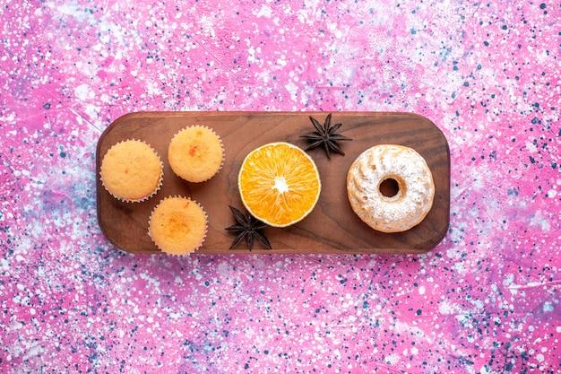 Vista dall'alto di piccole torte con fetta d'arancia sulla superficie rosa