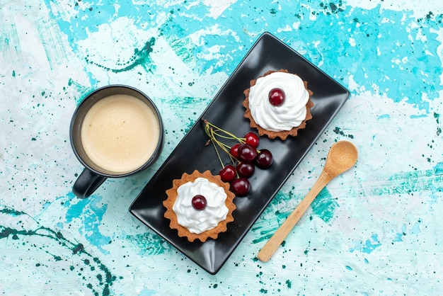 Vista dall'alto piccole torte con crema di frutta zucchero in polvere insieme a ciliegie latte su sfondo chiaro torta crema frutta tè dolce