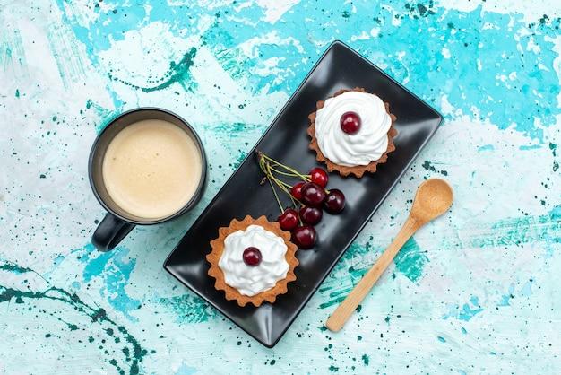 トップビューライトバックグラウンドケーキクリームフルーツスウィートティーにチェリーミルクと一緒に砂糖粉フルーツクリームと小さなケーキ