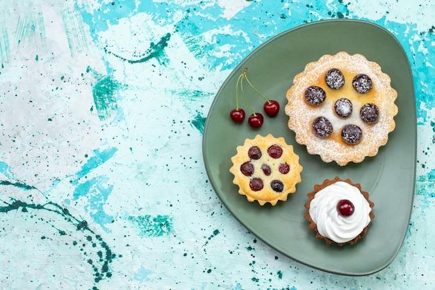 明るい背景の緑のプレートの中に砂糖粉フルーツクリームと小さなケーキの上面図ケーキクリームフルーツスウィートティー