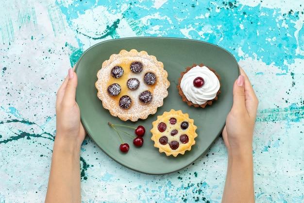 上面図青いテーブルケーキクリームフルーツスウィートティーのプレート内に砂糖粉フルーツクリームが入った小さなケーキ