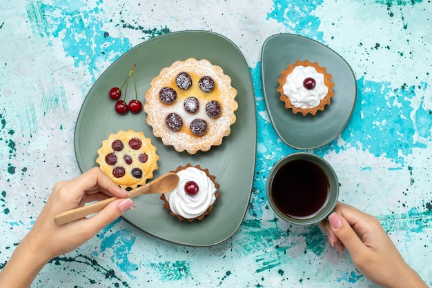 Top view little cakes with sugar powder fruits cream inside plate with tea on blue desk cake cream fruit sweet tea