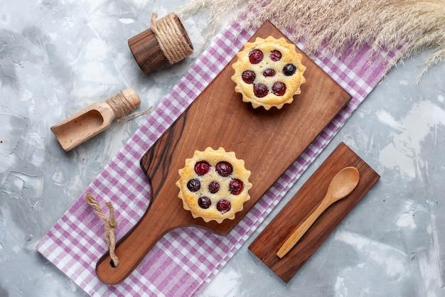 Vista dall'alto piccole torte con crema di frutta zucchero in polvere su tè dolce crema torta tavolo leggero