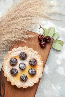 ライトテーブルの上の砂糖粉フルーツクリームと小さなケーキの上面図ケーキクリームフルーツスイート