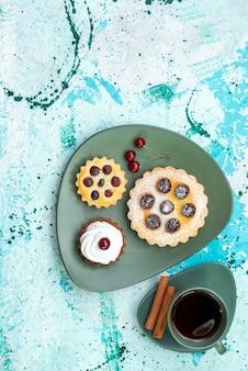 Вид сверху маленькие пирожные с чаем и корицей на голубом столовом пироге с вишневым фруктовым сладким