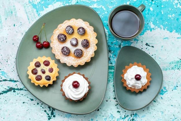 Vista dall'alto piccole torte con tè sulla torta di frutta ciliegia torta tavolo azzurro dolce