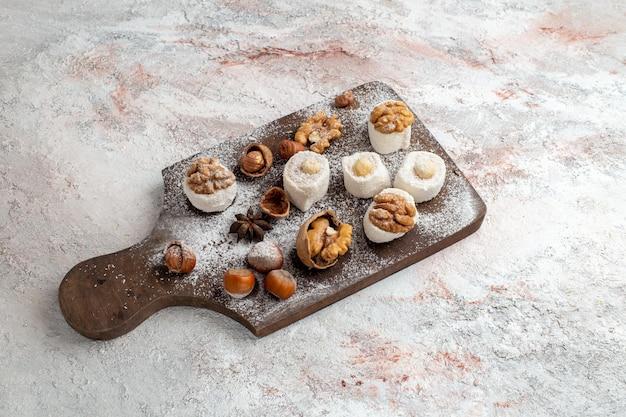 흰색 표면에 호두와 헤이즐넛이 있는 상위 뷰 작은 케이크
