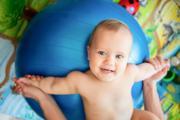 Top view of little caucasian kid enjoying exercises on big blue fitness ball